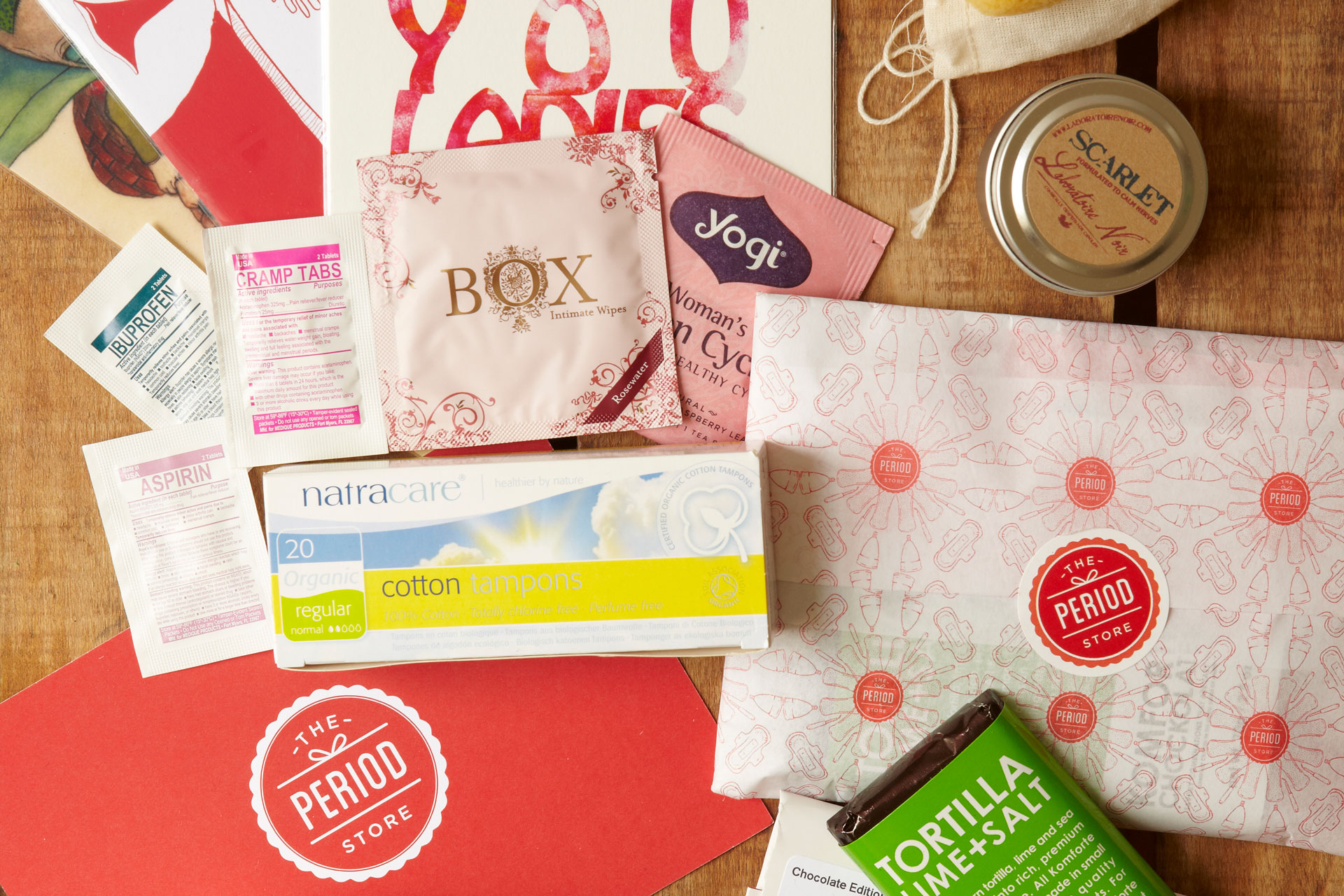 Red box from The Period Store with cotton natracare tampons, teas, chocolate, and more.